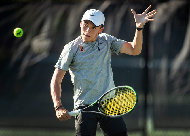 Lakeland junior Sam Reeder hits a backhand volley at the net while playing Orlando East Ridge's Zip Parel during a Class 3A regional semifinal tennis match at Beerman Family Tennis Center.