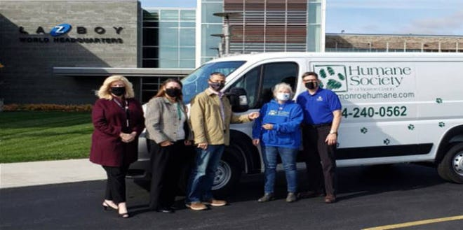 Humane Society of Monroe County and La-Z-Boy Foundation officials celebrate the purchase of a van using La-Z Boy Foundation funds to serve Monroe County's animal care and animal control needs.