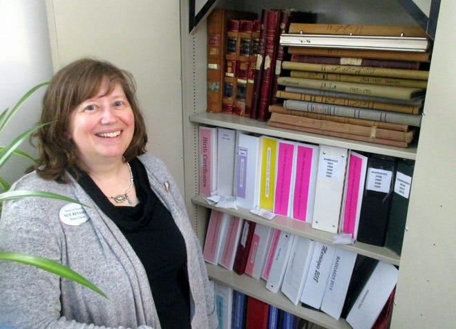 As part of her job as Hamilton's town clerk, Sue Reymers looks after the vintage town records stored in fireproof cabinets at the new town hall on Milford Street.