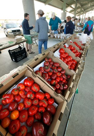 Customers buy fresh vegetables during a previous year's Edmond Farmers Market at Festival Market Place in downtown Edmond.