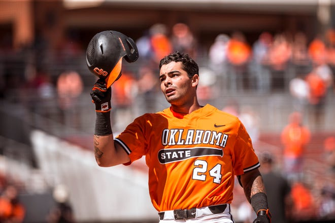 Oklahoma State's Christian Encarnacion-Strand removes his helmet to celebrate with his teammates after scoring a run earlier this season against North Carolina-Wilmington.