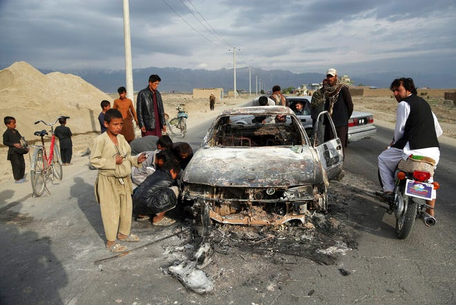 In this Tuesday, April 9, 2019, photo, Afghans watch a civilian vehicle burned after being shot by US forces after an attack near the Bagram Air Base, north of Kabul, Afghanistan. The U.S. military has begun shipping equipment and winding down contracts with local service providers ahead of the May 1 start of the final phase of its military pullout from Afghanistan, a U.S. Defense Department official said Thursday, April 22, 2021.