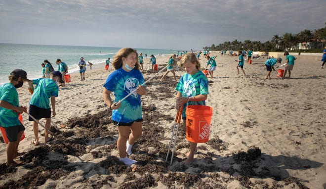 """Fifth-grade students Bea George, 12, left, and Annabelle Carden, 11, and their Rosarian Academy classmates team up with Friends of Palm Beach on Thursday to clean up Midtown Beach for Earth Day. """"We've been learning a lot in class about ecosystems and how everything is connected,"""" said Rosarian Academy science teacher Cassie Klein. In Washington, President Joe Biden pledged to cut the United States' carbon emissions 52% by 2030. More photos, page XX"""