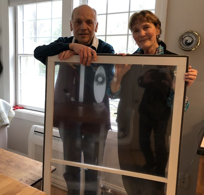 Nick and Maggie Bartenhagen are seen here with an insert they built for their Kennebunk home with Window Dressers, a nonprofit organization that helps people keep their homes warm, save money, and reduce their carbon footprint in the environment. Another one of their inserts is installed in the window behind them, on the left.