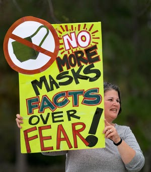 Anti-mask demonstrator Jennifer Showalter holds a sign outside the Palm Beach County School District offices during a school board meeting on April 21, 2021 in West Palm Beach, Florida.