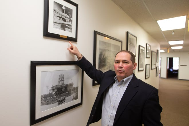 Tim Shultz, a partner at Goodell, Stratton, Edmonds & Palmer LLP, points to photos Monday that take viewers through the history of the Topeka law firm. Though its name has changed over the decades, what is now Goodell, Stratton, Edmonds & Palmer has been in business for 140 years.