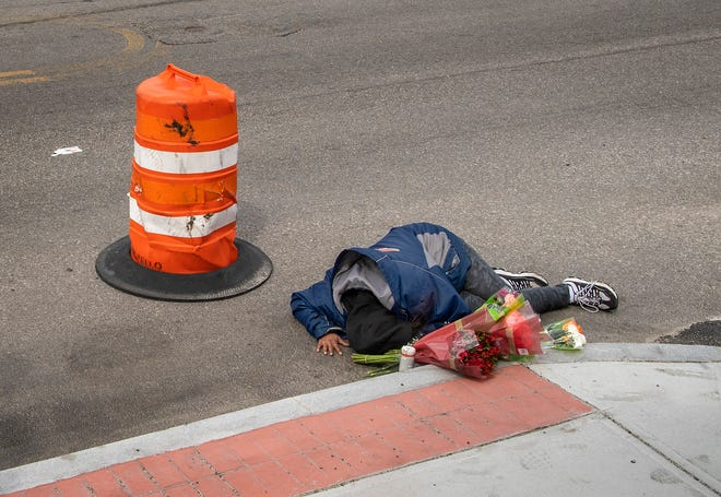 AnnMarie Gonzalez cries on the spot on Grafton Street in Worcester Thursday where her son Phet Gouvonvong, 31, was shot and killed by police early Wednesday.