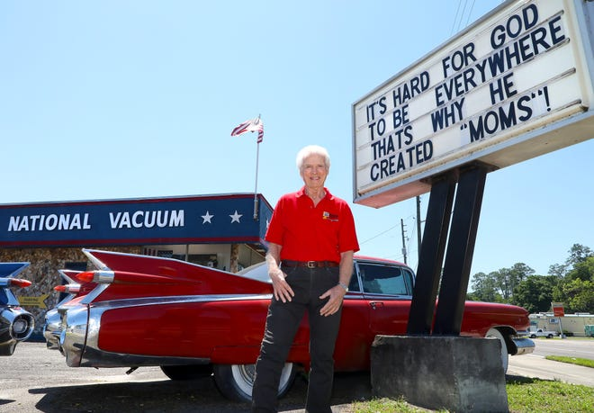 Bob deRochemont, who owns National Vacuum and has posted messages on the sign outside his shop for more than 40 years, stands by the sign and the Cadillac that has made his store an iconic Gainesville spot, on the corner of Northwest Sixth Street and Northwest 23rd Ave., on Thursday in Gainesville.