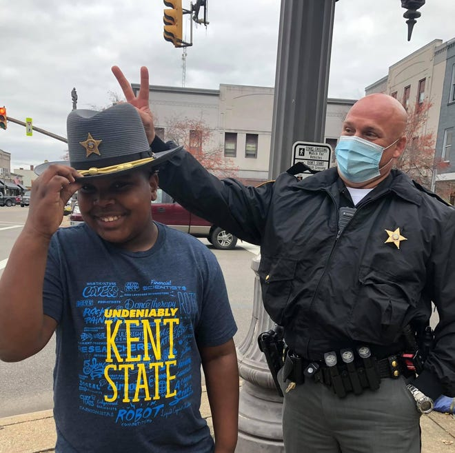 Amir McClelland (left) tried on the hat of Lt. Brian Alford (right) while the deputy was working at an Oct. 24 protest at the Tuscarawas County Courthouse. His guardian Traci Buzzeo of snapped the photo after she and Amir, 12, decided to take coffee to the deputies.