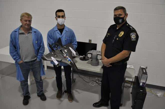 Andrew Merz, a mechanical and material engineer at Converge Technologies, holds a prototype of a drone first responder with John Bair, CEO and CTO of Converge Technologies, and Hilliard police Deputy Chief Eric Grile.