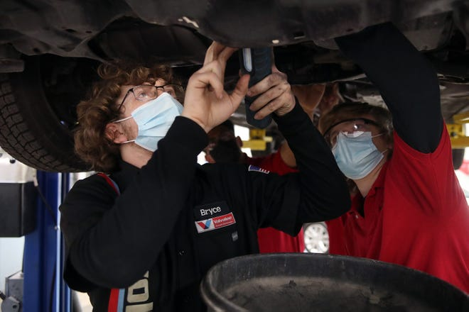 Automotive-technology students Bryce Eddy (left), 17, and Johnny Beverly, 18, prepare to drain coolant from a vehicle during class April 21 at the South-Western Career Academy in Grove City.