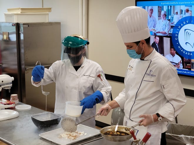 Culinary arts student Abbigail Phillips, of Marion High School, makes bananas Foster with Ben Loomis from the Niagara Falls Culinary Institute.