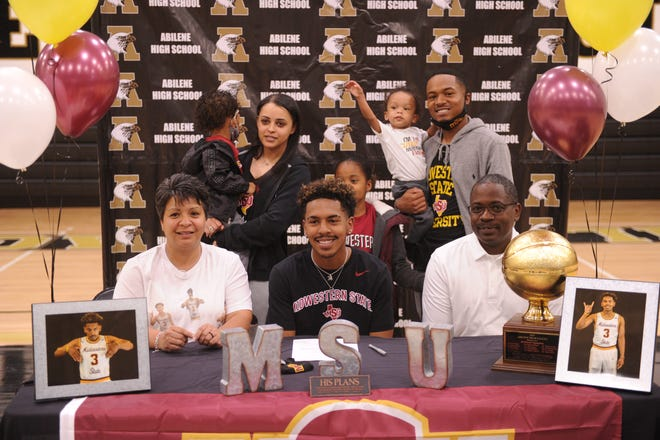 Abilene High senior Jalen McGee, front and center, signed to play basketball at Midwestern State on Thursday at Eagle Gym. His brother Calvin, back right, also played basketball at AHS. He signed with McMurry his senior year in 2015.