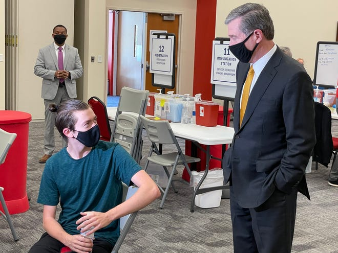 Gov. Roy Cooper speaks with Ian Towers, 17, after he received his first dose of the Pfizer COVID-19 vaccine at Buncombe County's first-dose vaccination site at A-B Tech April 22.