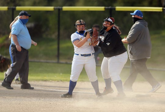 Bremerton's Marli Stodden (14) and Shyanna Dew (25) celebrate an out at first against North Mason on Wednesday.