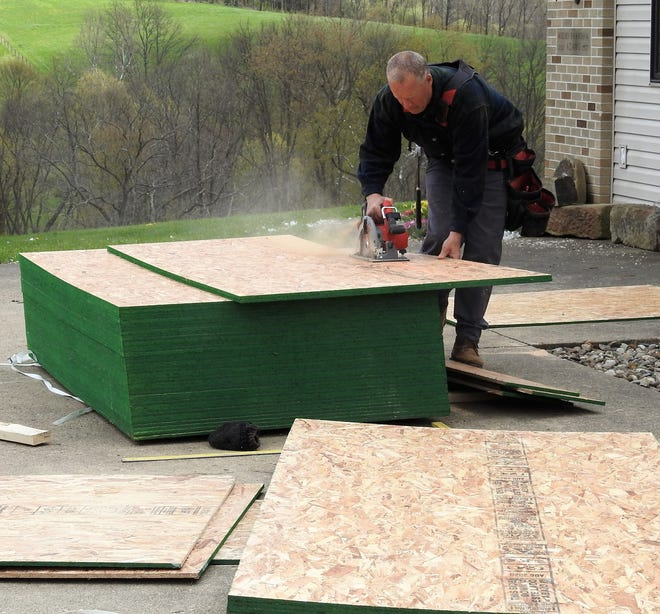 Tim Eberhard of Cross Builders cuts materials for a roofing project on Ohio 621. Business for contracts is booming right now, which has also led to a scarcity of materials and a price hike, Eberhard said.