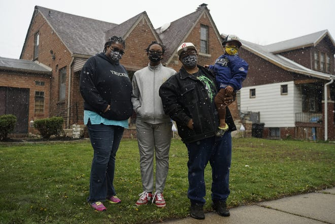 From left, Alexandria McCurtis, Xavier Johnson, Darius McCurtis and Sebastian McCurtis, outside their Detroit home on April 20, 2021. The couple owes more than $7,700 in back property taxes on their home that has been in their family since the 1970s. City officials launched a program last year aimed at helping get people out of debt called Pay As You Stay, but the couple said their income exceeds the program's limits.