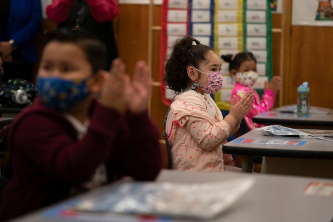 """FILE - In this April 13, 2021, file photo, first graders applaud while listening to their teacher in a classroom on the first day of in-person learning at Heliotrope Avenue Elementary School in Maywood, Calif. California's public schools have seen a """"sharp decline"""" in enrollment this year as the pandemic forced millions into online school and districts dawdled in bringing children back to the classroom. Data from the California Department of Education released Thursday, April 22, 2021, shows the number of students at K-12 schools dropped by more than 160,000 this academic year, most of them in K-6. (AP Photo/Jae C. Hong, File)"""