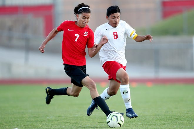 Palm Springs' Kevin Reyes, left, dribbles the ball as Palm Desert's Carlos Chaparro defends in Palm Springs, Calif., on April 21, 2021.
