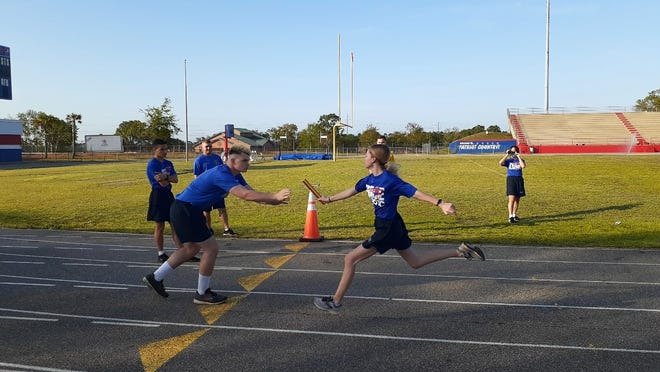 Members of Pace High School's JROTC team compete in a 100-yard relay as part of a national championship competition. The team finished second overall in the race portion but first overall for the championship.