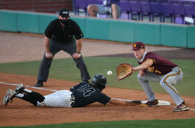 Grand Canyon University infielder Channy Ortiz (14) dives safely back to first as Arizona State University infielder Jack Moss (7) fields the throw during the third inning at GCU Ballpark in Phoenix April 21, 2021.