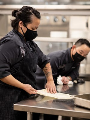 In a video lesson, Famous Foods Street Eats Executive Chef Kevin Hee and assistant chef Angela Ng practiced flipping dough to make authentic Roti Canai from Singapore hawker Springleaf Prata.