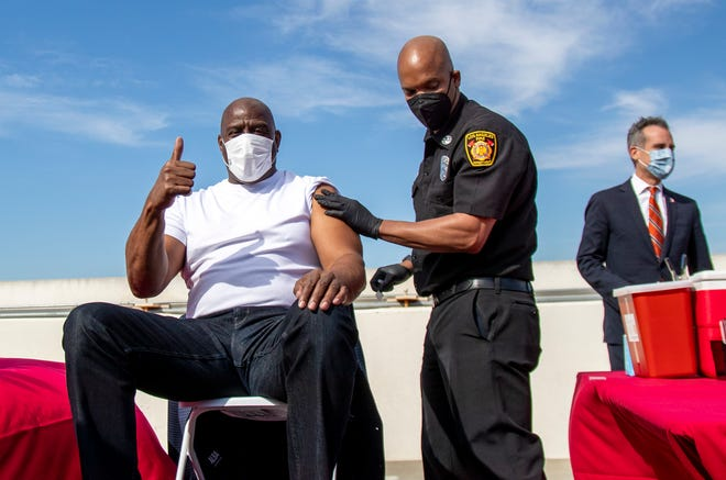 Magic Johnson (left) gives a thumbs-up after getting a vaccine last month, as a part of a vaccination awareness event at USC, in Los Angeles.