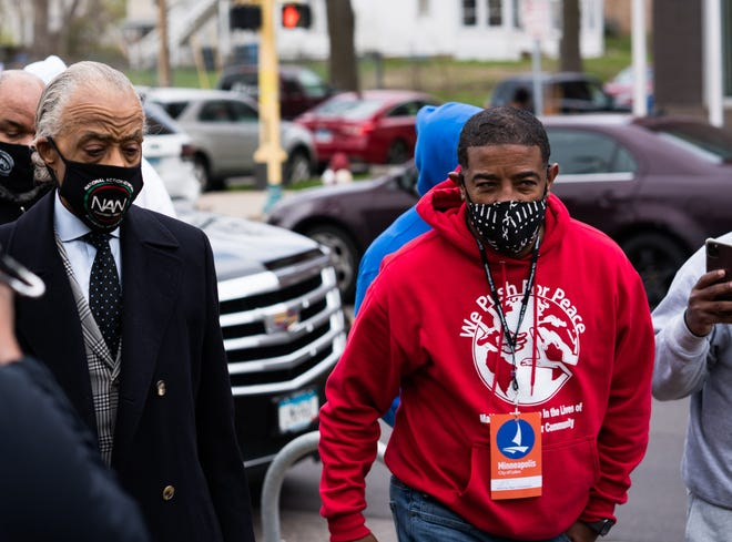 Trahern Pollard of We Push for Peace, a community-based anti-violence group, escorts the Rev. Al Sharpton into the memorial viewing of Daunte Wright in Minneapolis. Wright was shot and killed by police in nearby Brooklyn Center, and the viewing was held the day after a jury convicted former Minneapolis police Officer Derek Chauvin in the murder of George Floyd.