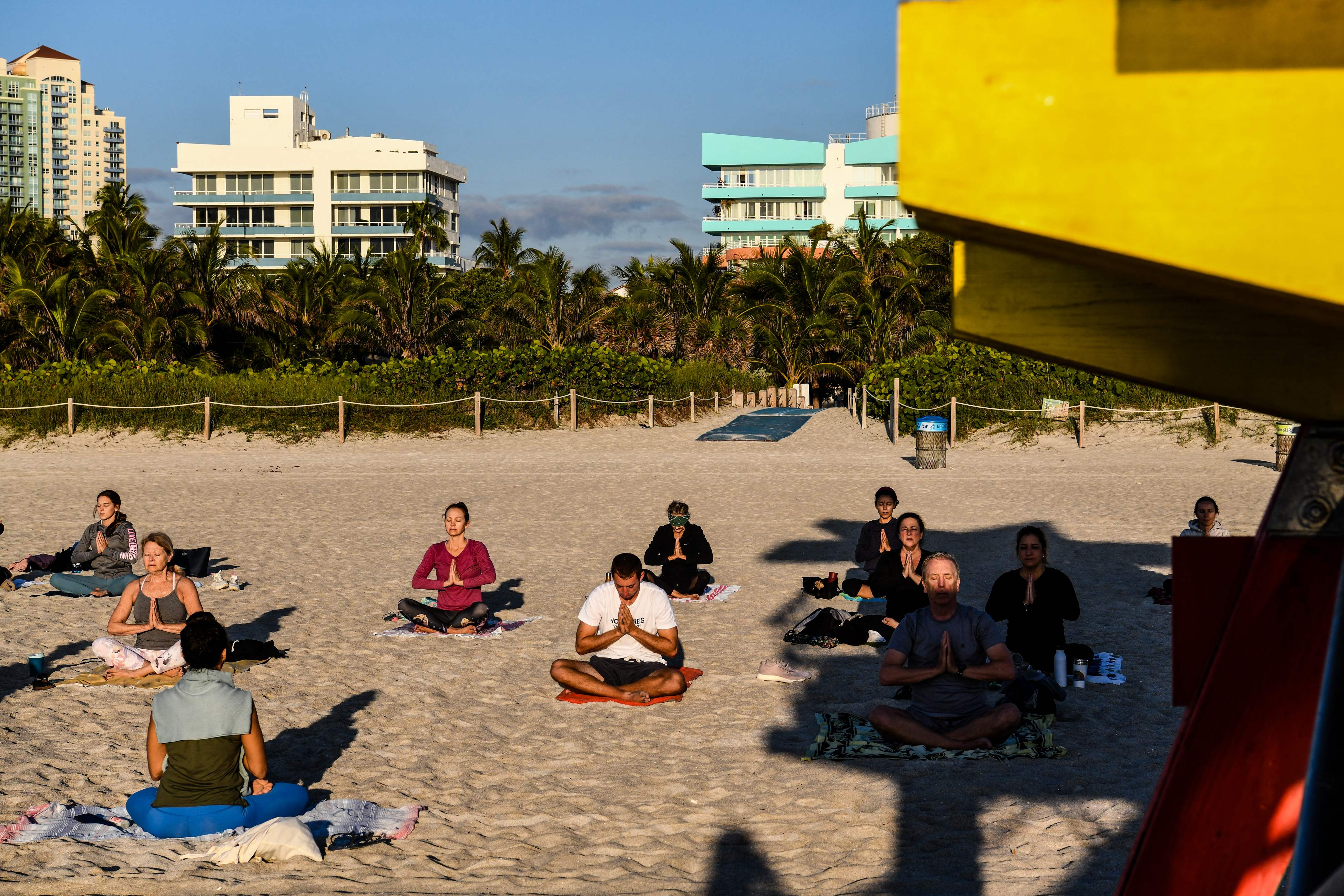 A group of people participate in a yoga session taught by Radha Silva on the beach in Miami Beach, Florida, on March 23, 2021.