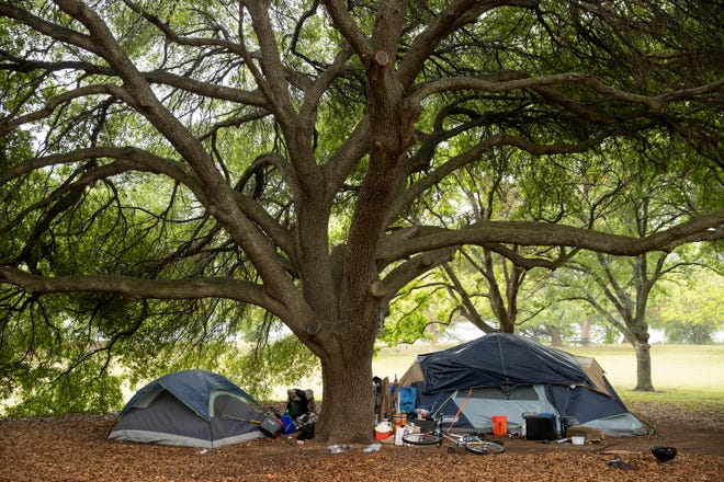 Homeless people live in tents under a tree in Edward Rendon Sr. Metro Park at Festival Beach on April 23.