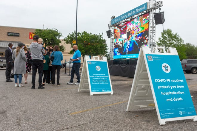 Walmart shoppers and Texas Department of State Health Services staffers stand near a 16-foot screen promoting COVID-19 vaccinations Thursday, part of a statewide effort to encourage more Texans to get vaccinated as demand declines.