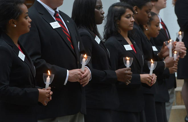 Members of the UGA Arch Society hold candles during a campus vigil for members of the University of Georgia community who died in the past year on Tuesday, April 29, 2014, in Athens, Ga. (File photo)