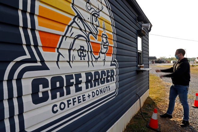 A customer grabs coffees from Cafe Racer in Crawford, Ga., on Friday April 23, 2021. The coffee, doughnut, biscuits and burger spot has become a go-to destination for Athens locals during the pandemic.