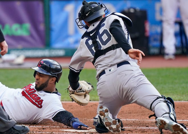 Cleveland's Eddie Rosario, left, slides safely into home plate as New York Yankees' Kyle Higashioka is late on the tag in the first inning of a baseball game, Thursday, April 22, 2021, in Cleveland. [Tony Dejak/Associated Press]