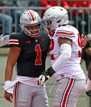 OSU quarterback Justin Fields (1) is congratulated on his touchdown by Wyatt Davis (52) during The Ohio State Spring Game at the Ohio Stadium in Columbus, Ohio on April 13, 2019.  [ Brooke LaValley / Dispatch ]