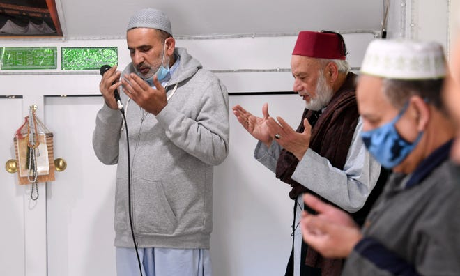 Mohammad Rafiq, center, and Asif Bagwa , left, pray for the general good at the end of the Ramadan service at the Cape Cod Mosque in Osterville Friday afternoon.