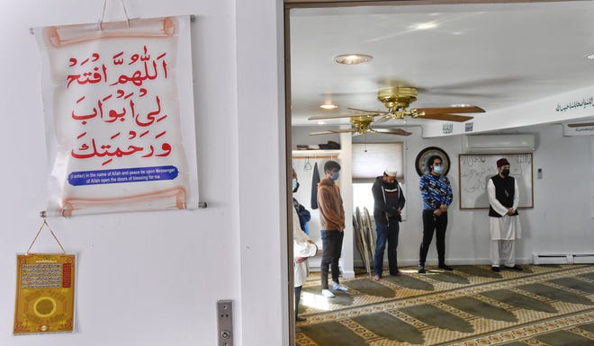 """Worshippers pray during a Ramadan service Friday at the Cape Cod Mosque in Osterville. The sign outside the prayer room says, """"(I enter) in the name of Allah and peace be upon Messenger of Allah open the doors of blessing for me."""" Because of the pandemic, the social aspect of the holiday has changed, with many Muslims deciding to eat by themselves and stay at home."""