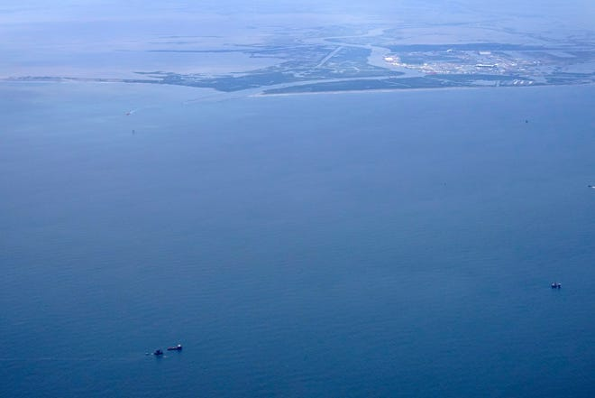 The capsized lift boat Seacor Power and two rescue boats, bottom left, are seen April 19 about 8 miles off Lafourche Parish in Gulf of Mexico. The vessel capsized during a storm April 13. Port Fourchon and Bayou Lafourche, where the ship left port, are seen at upper right.