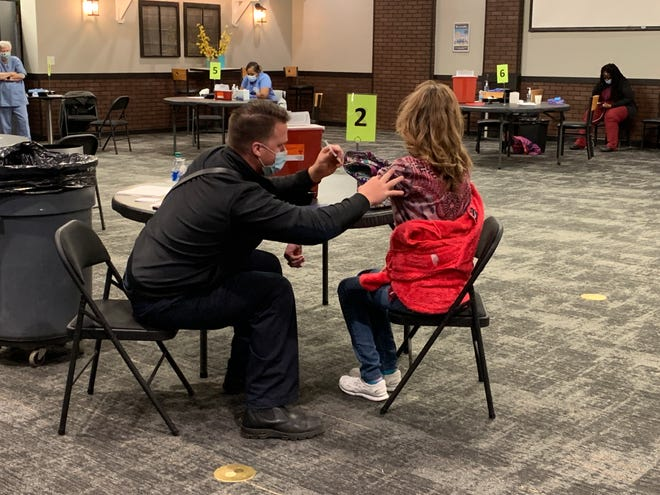 Chippewa Township firefighter/paramedic Mike Eisenhauer administers a shot at the walk-in vaccine held at Crossroads Community Church in Doylestown on Friday.