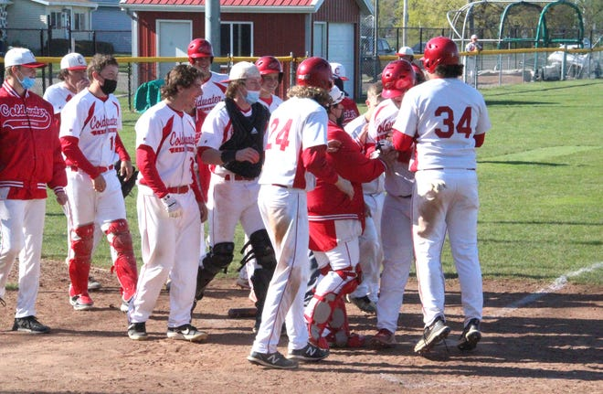 Coldwater's Brynden Massey is mobbed by his teammates at home after blasting a deep home run to left field in the Cardinals win over Hastings Thursday