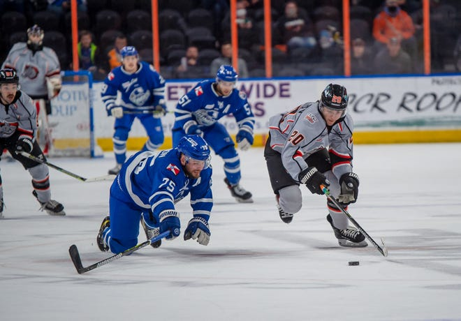 Kansas City Mavericks forward Nick Pastujov (20) tries to outrace Wichita defenseman Mathieu Gagnon (75) to the loose puck in Thursday's game at Cable Dahmer Arena. Wichita scored four third-period goals to break open a tight game for a 6-1 win.
