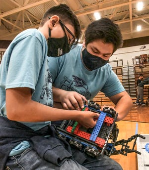 Justin Contreras, left, and Alex Argueta work on their robot prior to one of the rounds in a state robotics competition at GCHS. Both are eighth graders at Kenneth Henderson Middle School.