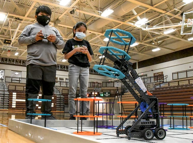 Erik Ramirez, left, uses a controller to have a robot lift an object and move it on the playing field Saturday as his teammate, Camila Hernandez, looks on April 17 during a state robotic competition in the Garden City High School competition gym.  The pair are fourth graders at Buffalo Jones Elementary School. The tournament featured 19 teams competing.