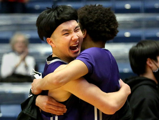 Ranger's Keisei Tominaga (30) hugs teammate Tiras Morton (5) after their team defeated South Plains 87-83 in overtime during the NJCAA Men's Div I Basketball Championship Tournament Thursday. Tominaga scored 25 points which inlcuded five 3-point shots.