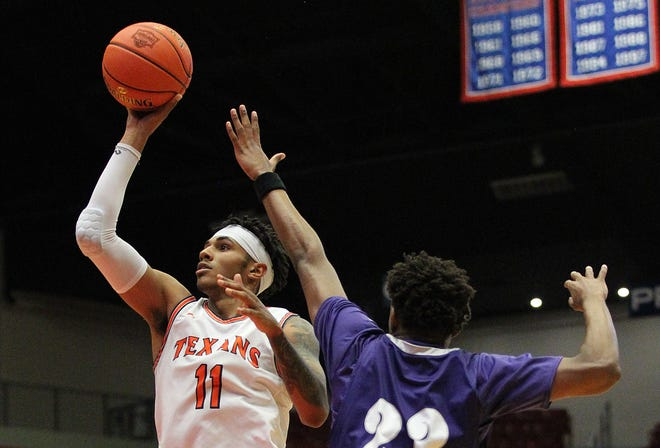 South Plains' Rivaldo Soares (11) shoots past Ranger's Jorell Saterfield (23) during their NJCAA Men's Div I Basketball Championship Tournament Thursday at the Sports Arena in Hutchinson. South Plains lost to Ranger 87-83 in overtime.