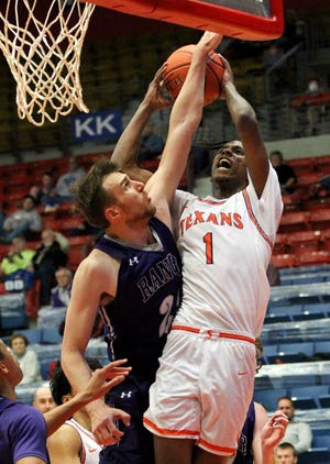 South Plains College's Philmon Gebrewhit (1) shoots over Ranger's Nika Metskhvarishvili during the Texans' 87-83 overtime loss to the Rangers on Wednesday night in the NJCAA Tournament.