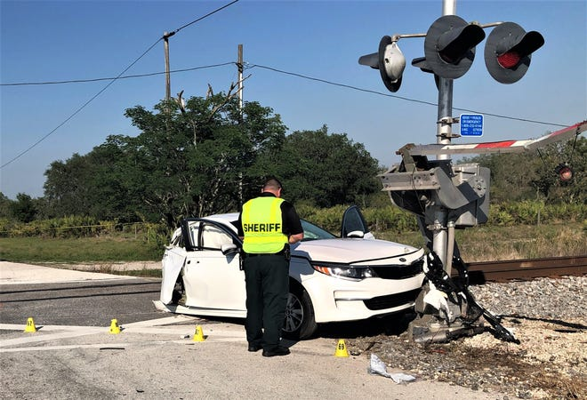 An investigator with the Polk County Sheriff's Office examines the Kia sedan that was struck by an Amtrak train near Frostproof on Thursday afternoon.