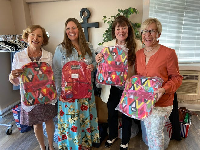 Some of the donated backpacks held by Jane Wright, Laura Gartin (from Live 2 Give Hope), Nancy Boland, Debby Nickless.