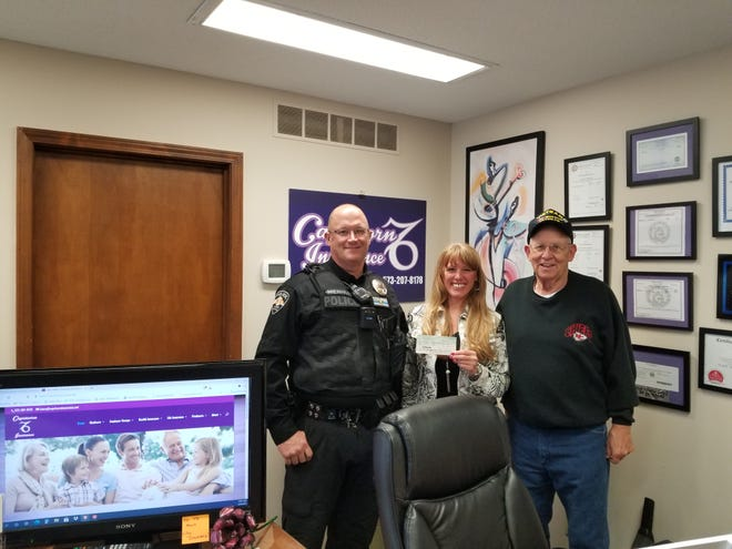 Pictured: Police Chief Mike Nienhaus, Laura Peretic owner of Capricorn Insurance & City of Laurie Mayor, Allen Kimberling.