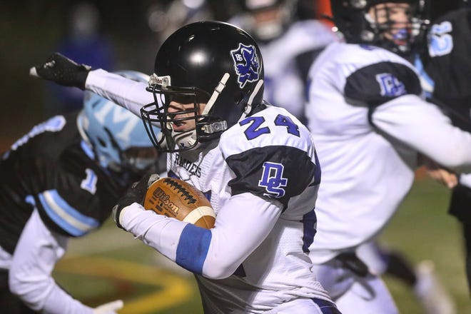 Dover-Sherborn senior Nick Rinaldi runs the ball during the football game against Medfield at Medfield High School on Apr. 22, 2021.